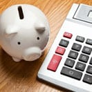 white piggy bank beside desk calculator