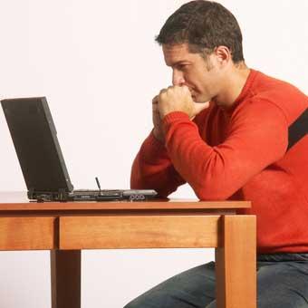 man looking at computer, sitting at table