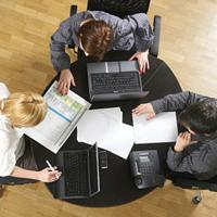 Three people working around a desk
