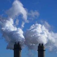 Two chimneys spewing smoke