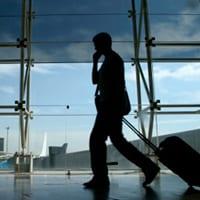 Man on a mobile phone, walking through an airport