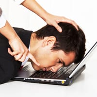 Man with head shoved on computer