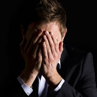 Depressed employee with hands over his face