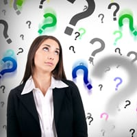 Businesswoman surrounded by question marks