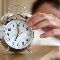 man reaching for clock