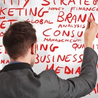 Man writing business terms on a whiteboard