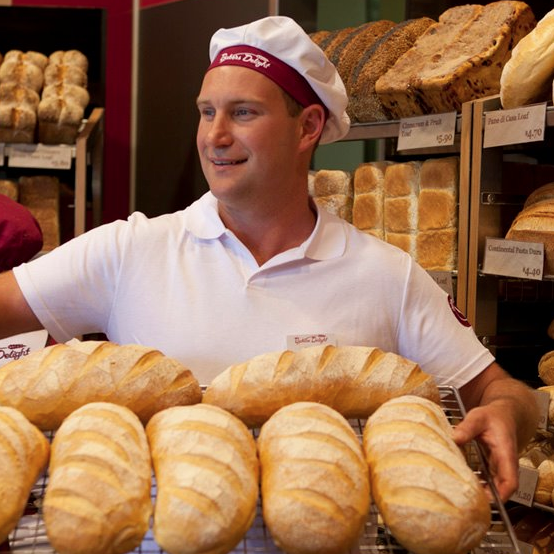 Bakers Delight employee holding up tray of bread