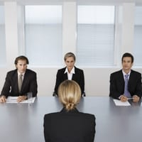 woman in a job interview, sitting face-to-face with three interviewers