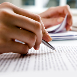 Woman holding pen over business documents