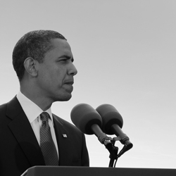 Barack Obama, standing in front of microphones