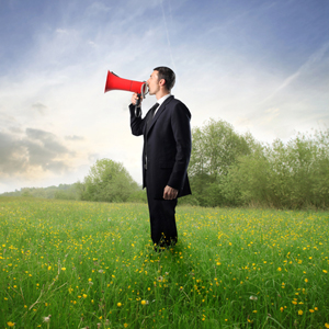 Business man on megaphone, in a field of grass