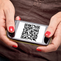 Woman holding a mobile phone with a QR code on its screen