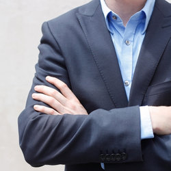 business man with arms crossed in front of him