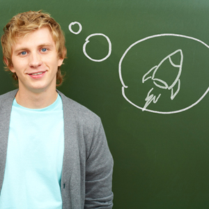 Young man standing in front of blackboard, with an idea bubble