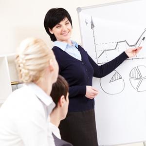 Woman making speech, in front of whiteboard