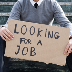 """Man holding up a sign reading """"Looking for a job"""""""