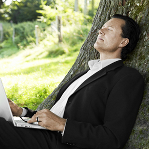 Business man dreaming under trees