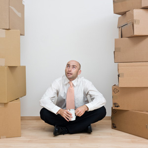 Man sitting between two towers of boxes