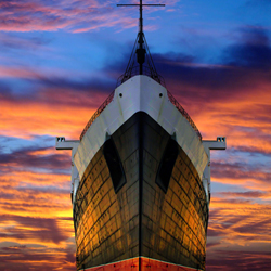 Giant ship in front of colourful sunset