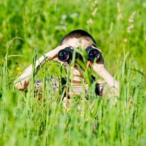 Little boy in long grass, with binoculars