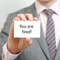 """Man holding up """"You are Fired"""" business card"""
