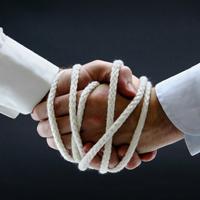 Men, shaking hands, with ropes bound around hands