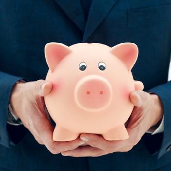businessman holding pink piggy bank