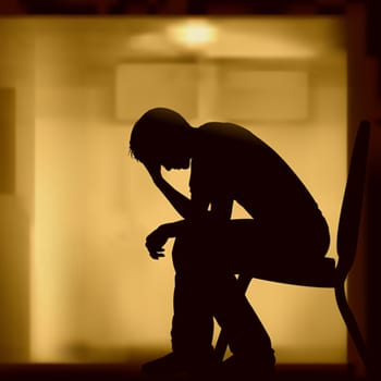 Silhouette of an upset man, sitting on a chair