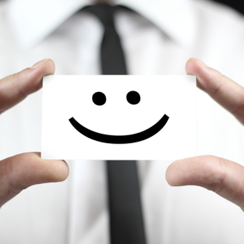 Smiley face on a card, being held up by businessman