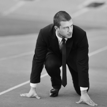 Business man, crouched at a race starting line