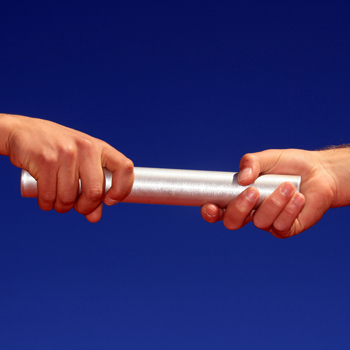 Two hands passing a silver baton
