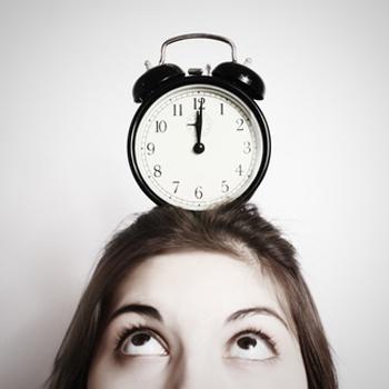 Woman with alarm clock on head