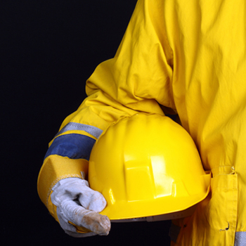 Man dressed in safety gear, holding a hard hat