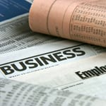 business news in pile of newspapers