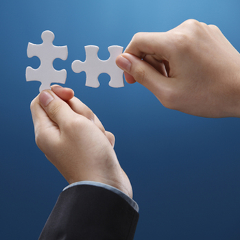 Businessman putting two jigsaw pieces together