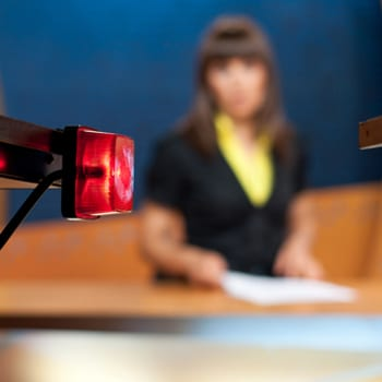 Newsreader sitting behind camera