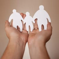 Paper doll family in hands