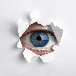 Eye peeping through a hole in white wall