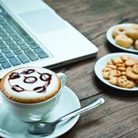 cappucino and biscuits next to computer