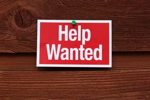 help wanted sign on wooden background