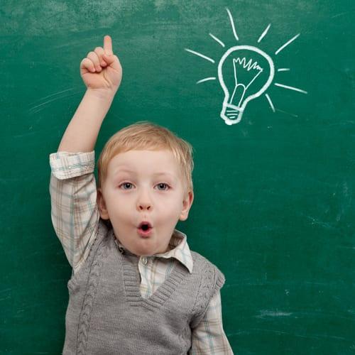 little boy in front of chalkboard with light globe