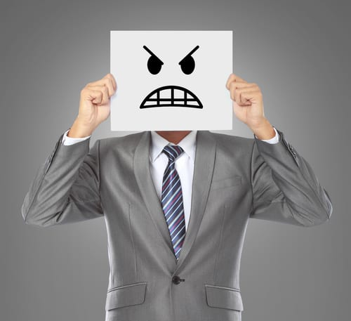 businessman holding angry face sign in front of him
