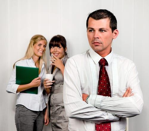 two women talking behind man's back