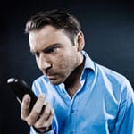 man looking angrily at a mobile phone