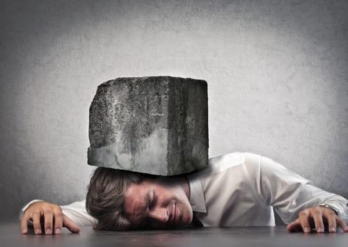 man under block of stone